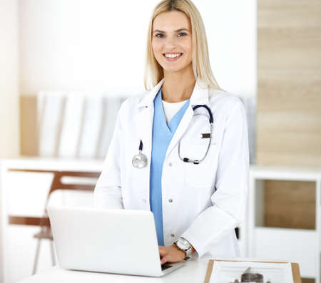 Woman-doctor controls medication history records and exam results while using laptop computer in sunny hospital. Medicine and healthcare concept