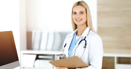 Doctor woman controls medication history records and exam results while using clipboard in sunny hospital . Medicine and healthcare concept