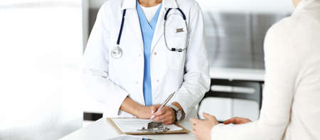 Unknown woman-doctor and patient in hospital. Blonde physician controls medication history records and exam results while using clipboard, close-up. Medicine concept
