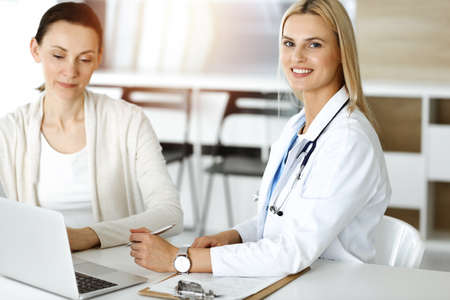 Woman-doctor at work in sunny hospital is happy to consult female patient. Blonde physician checks medical history record and exam results while using clipboard