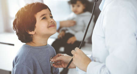 Doctor-woman examining a child patient by stethoscope in sunny clinik. Cute arab boy and his brother at physician appointment