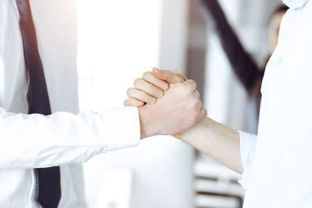 Two businessmen shaking hands in sunny office, close-up. Happy and excited business woman stands with raising hands at the background. Business people concept
