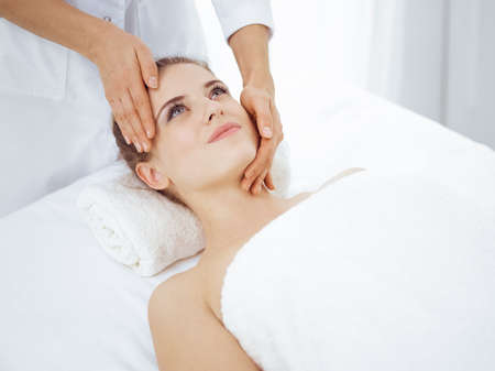 Young and blonde woman enjoying facial massage in spa salon. Beauty concept Stock fotó