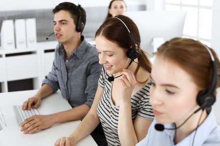 Casual dressed young woman using headset and computer while talking with customers online. Group of operators at work. Call center, business concept Reklamní fotografie