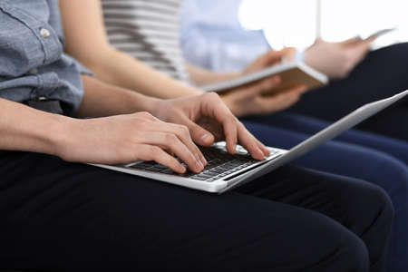 Group of casual dressed business people working at meeting or conference, close-up of hands. Businessman using laptop computer. Teamwork or coaching concept