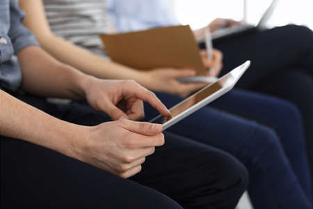 Group of casual dressed business people working at meeting or conference, close-up of hands. Businessman using tablet computer. Teamwork or coaching concept Reklamní fotografie