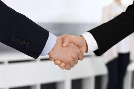 Businessman and woman shaking hands in office. Concept of handshake as success symbol in business