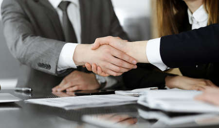 Unknown businessman shaking hands with his colleague or partner above the glass desk in modern office, close-up. Business people group at meeting