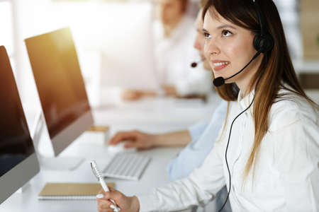 Asian woman working at customer service office. Business concept. Group of diverse operators at work in sunny call center. Stock Photo