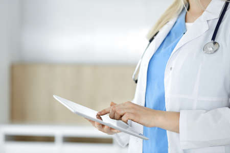 Unknown woman-doctor standing in clinic and using tablet pc, close-up. Data in medicine and healthcare 版權商用圖片