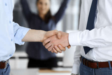 Two businessmen are shaking hands in office, close-up. Happy and excited business woman stands with raising hands at the background. Business people concept