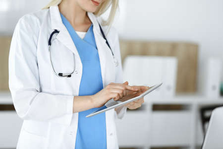 Unknown woman-doctor standing in clinic and using tablet pc, close-up. Data and best service in medicine and healthcare 版權商用圖片