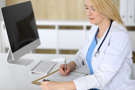 Doctor woman at work while sitting at the desk in hospital or clinic. Blonde cheerful physician filling up medical records form. Data and best service in medicine and healthcare