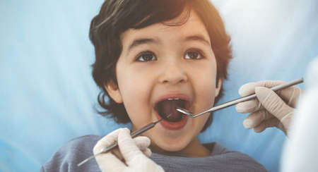 Cute arab boy sitting at dental chair with open mouth during oral checking up with doctor. Visiting sunny dentist office