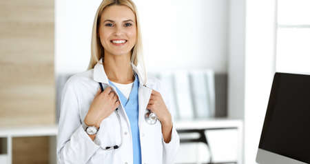 Blond female physician is standing at her workplace near desktop computer. Woman-doctor is excited and happy of her profession. Medicine concept
