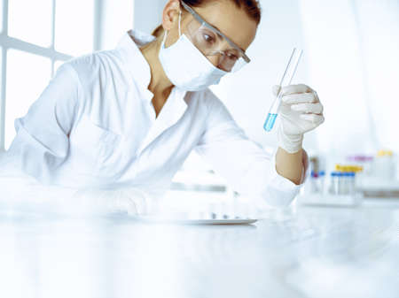 Female laboratory assistant analyzing test tube with blue liquid. Medicine, health care and researching concept