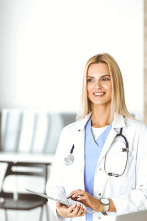 Woman-doctor at work in clinic excited and happy of her profession. Blond female physician is smiling while using tablet computer. Medicine concept