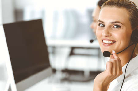 Blond female customer service representative and her colleague are consulting clients online using headset. Call center and business people concept