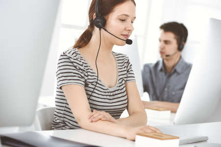 Casual dressed young woman using headset and computer while talking with customers online. Group of operators at work. Call center, business concept