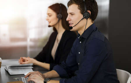 Call center operators at work. Two young people in headsets are talking to the clients, while sitting in sunny office
