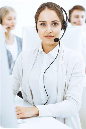 Call center. Group of diverse operators at work. Beautiful woman in headset communicating with customers of telemarketing service. Business concept