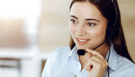Brunette female customer service representative using headset and consulting clients online. Call center
