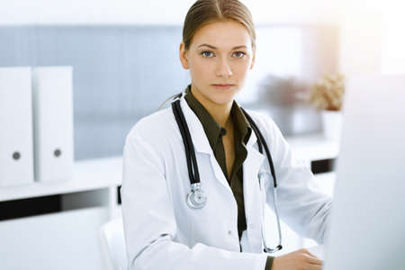 Woman-doctor typing on pc computer while sitting in sunny hospital office. Data in medicine and healthcare Archivio Fotografico