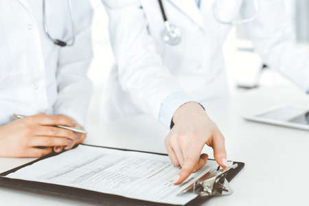 Unknown woman-doctors at work with patient at the background. Female physicians filling up medical documents or prescription while standing in hospital reception desk, close-up. Health care concept