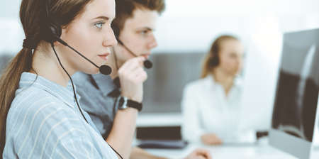 Call center. Group of casual dressed operators at work. Brunette business woman in headset at customer service office
