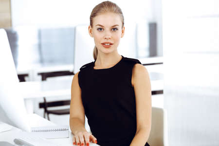 Young blond businesswoman working on computer while sitting at the desk in modern office. Business people concept. Black dress do suits to her much at this portrait Banque d'images