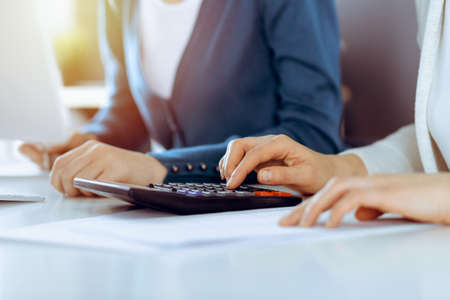 Accountant checking financial statement or counting by calculator income for tax form, hands closeup. Business woman sitting and working with colleague at the desk in office. Tax and Audit concept Zdjęcie Seryjne