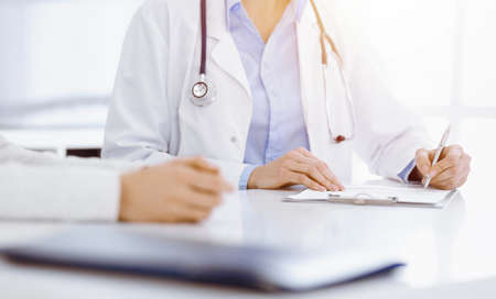 Unknown woman-doctor and female patient sitting and talking at medical examination in sunny clinic, close-up. Medicine concept