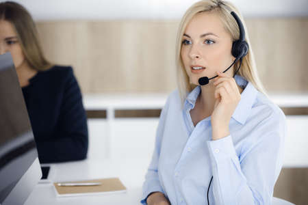 Blonde business woman sitting and communicated by headset in call center office. Concept of telesales business