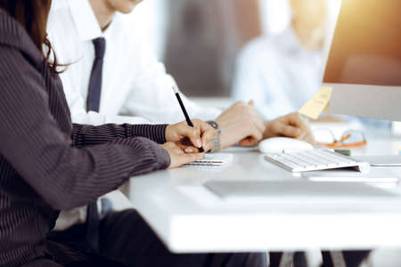 Business woman and man discussing questions while using computer and blocknote in sunny office, close-up