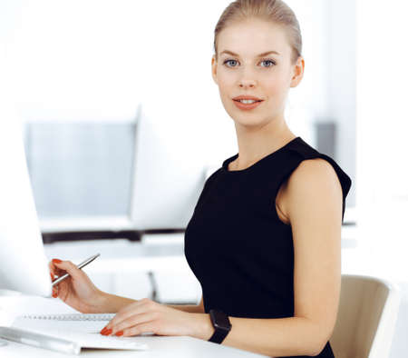 Young blond businesswoman working on computer while sitting at the desk in modern office. Business people concept. Secretary looks beautiful in black dress