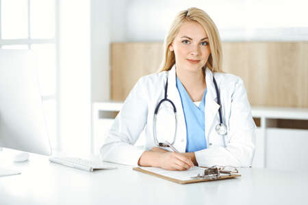 Woman-doctor at work while sitting at the desk in hospital or clinic. Blonde cheerful physician filling up medication history record form Stock Photo