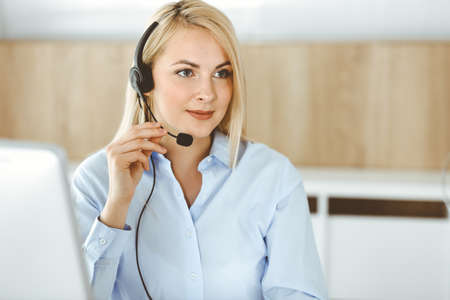 Blonde business woman sitting and communicated by headset in call center office. Concept of telesales business or home office occupation