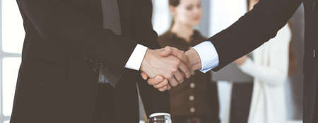 Business people shaking hands after contract signing while standing in a modern office. Teamwork and handshake concept