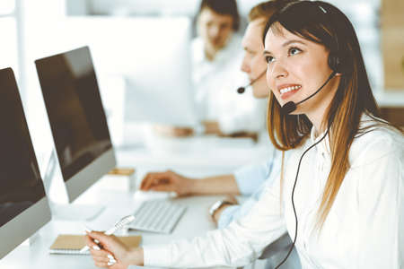 Group of diverse operators at work in call center. Beautiful asian woman sitting in headset at customer service office. Business concept