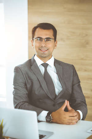 Cheerful smiling businessman sitting at a desk in sunny office. Business concept