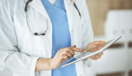 Unknown woman-doctor standing in clinic and using tablet pc, close-up. Data and best service in medicine and healthcare Foto de archivo