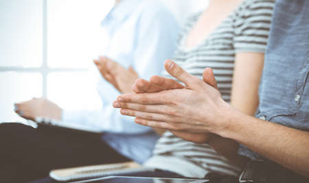 Business people clapping at meeting or conference, close-up of hands. Group of unknown businessmen and women in modern white office. Success teamwork, corporate coaching and applause concept