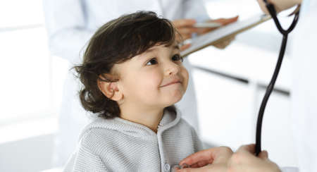 Woman-doctor examining a child patient by stethoscope. Cute arab toddler at physician appointment. Medicine concept Foto de archivo