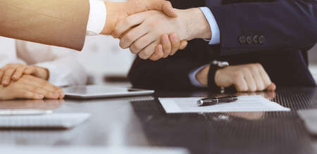 Handshake as successful negotiation ending, close-up. Unknown business people shaking hands after contract signing in modern office Foto de archivo