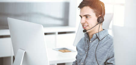 Casual dressed young man using headset and computer while talking with customers online in sunny office. Call center, business concept