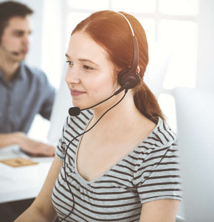 Casual dressed young woman using headset and computer while talking with customers online. Group of operators at work in sunny office. Call center