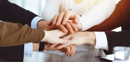 Business people group showing teamwork and joining hands or giving five in sunny office. Unknown businessman and women making circle with their hands