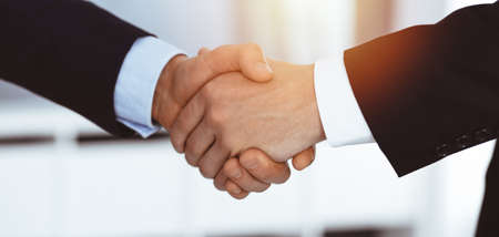Business people shaking hands after contract signing in sunny modern office. Teamwork and handshake concept