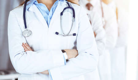 Group of modern doctors standing as a team with arms crossed in sunny hospital. Medical help, insurance in health care, best desease treatment and medicine concept