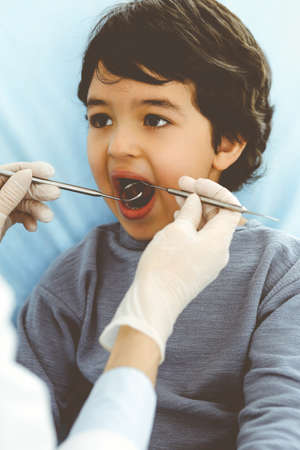 Little arab boy sitting at dental chair with open mouth during oral checking up with dentist doctor. Stomatology concept